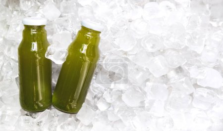 Green detox cocktail in glass bottle on ice cubes background