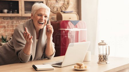 Photo for Full of gladness. Cheerful senior woman standing in kitchen, talking on phone and using her laptop, empty space - Royalty Free Image