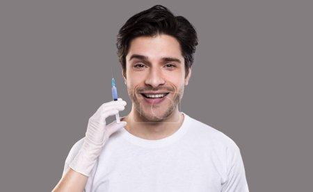 Photo pour Procédure cosmétique tendance pour les hommes. Jeune homme se faire injecter la beauté, fond de studio gris - image libre de droit