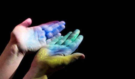 Photo pour Coloré holi peint femmes mains ouvertes pour la lumière sur fond noir, panorama, espace de copie - image libre de droit