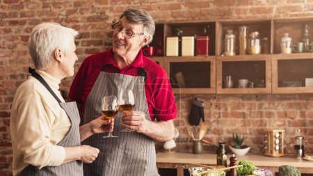 Photo for Happy married seniors enjoying evening glass of wine at kitchen, panorama, free space - Royalty Free Image
