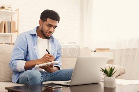 Photo pour Blogueur homme afro-américain ayant une excellente idée pour la publication, prendre des notes et regarder l'écran d'ordinateur portable à la maison, copier l'espace - image libre de droit