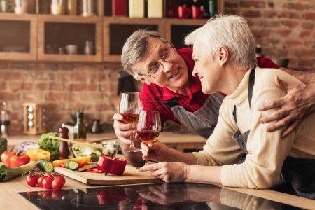 Photo pour L'apéritif du soir. Heureux homme et femme âgés embrasser, boire du vin à la cuisine, espace libre - image libre de droit