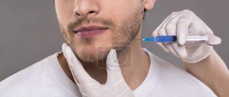 Photo pour Concept de chirurgie plastique. Jeune homme recevant une injection au visage, panorama - image libre de droit
