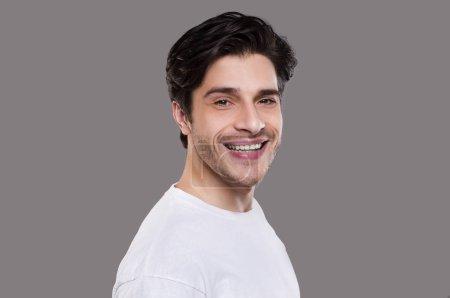 Photo pour Portrait semi-profil de mec caucasien joyeux sur fond gris - image libre de droit
