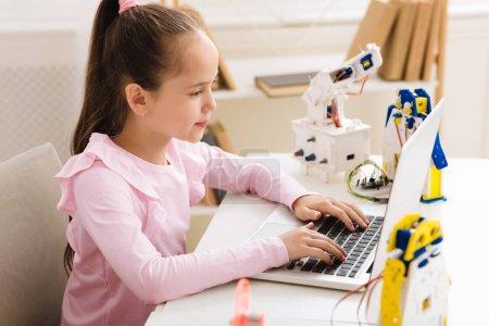 Photo pour Création d'un projet robotique. Fille dactylographier plan de robot modèle dans ordinateur portable, concept bricolage - image libre de droit