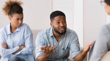 Photo pour Afro mari partageant des problèmes familiaux assis à côté de l'épouse insatisfaite au bureau des conseillers. panorama. - image libre de droit