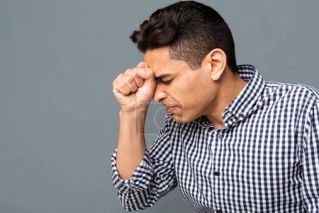 Photo pour Arabe homme pressant le poing serré au front dans le désespoir sur fond de studio gris. Espace de copie - image libre de droit
