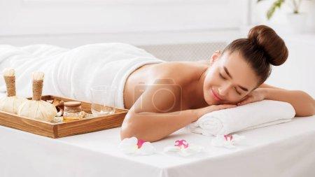 Photo pour Jeune femme relaxante avec composition aromatique à proximité, dans un salon de spa de beauté lumière - image libre de droit