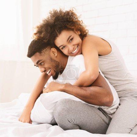 Photo pour Je l'aime tellement. Femme africaine gaie embrassant son petit ami au lit - image libre de droit