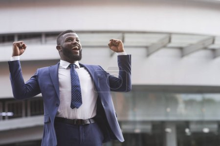 Photo for Happy excited black businessman celebrate victory with fists raised in the air staying against modern glass office center background, lifestyle portrait - Royalty Free Image