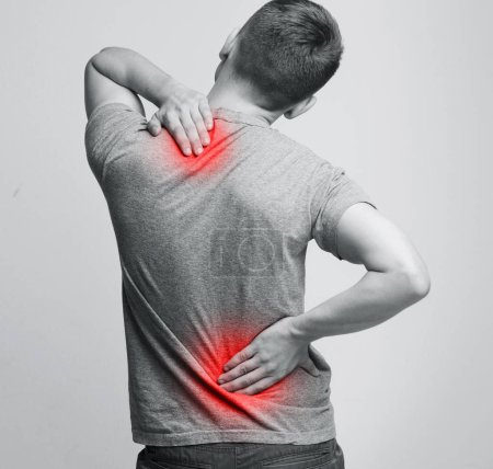 Photo for Man with neck and back pain, rubbing his painful body, back view - Royalty Free Image