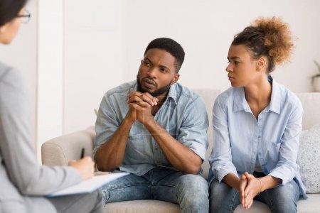 Photo pour Thérapie conjugale. Couples noirs écoutant aux conseils de conseillers s'asseyant sur le couch dans le bureau. - image libre de droit