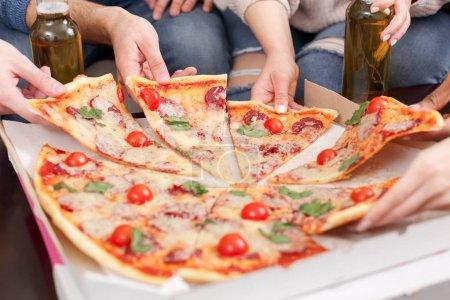 Photo pour Restauration rapide préférée. Amis prenant des tranches de délicieuse pizza, gros plan - image libre de droit