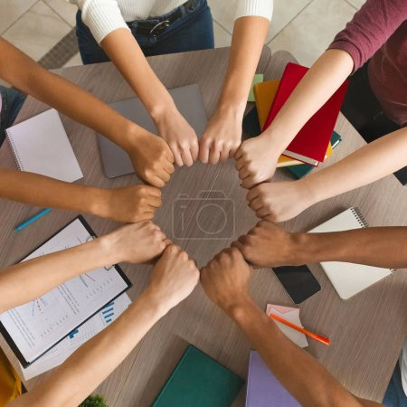 Photo for Group of international students joining hands together, preparing academic project, top view - Royalty Free Image