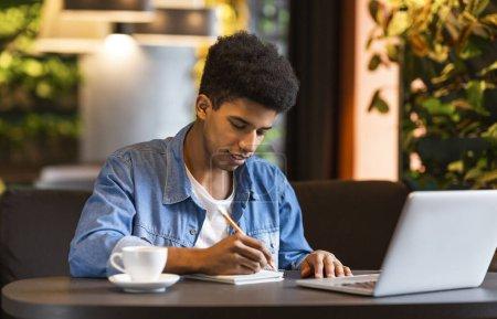 Photo pour Blogueur afro-américain de sexe masculin ayant une excellente idée pour la publication, prendre des notes au café, copier l'espace - image libre de droit