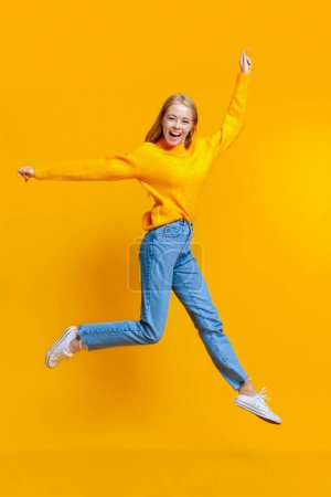 Photo for Jumping millennial girl in the air over orange studio background with free space - Royalty Free Image