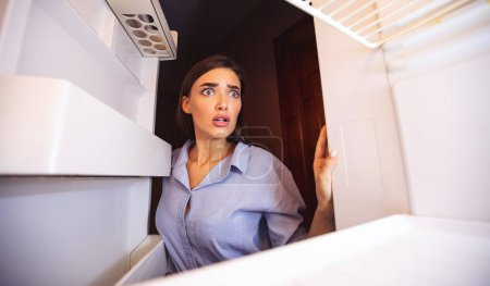 Photo for Coronacrisis concept. Shocked girl looking at her empty fridge shelves in despair, view from inside - Royalty Free Image