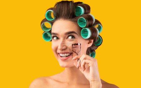 Photo pour Maquillage des yeux. Enthousiaste femme au foyer tenant cils Curler faisant beauté pose de routine sur fond jaune. Studio Shot - image libre de droit