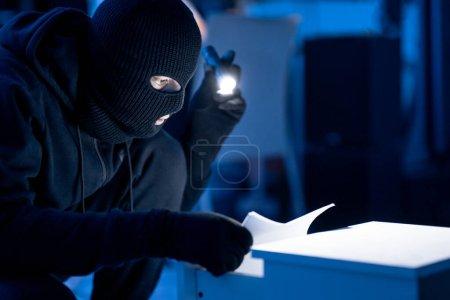 Photo pour Espionnage industriel. Intrus masqués tenant et lisant des documents confidentiels à l'aide d'une lampe de poche la nuit, espace de copie - image libre de droit