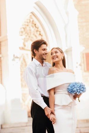 Photo pour Couple de mariage debout près de l'église, heureux après cérémonie minimaliste sans invités, tenant la main et étreignant. Vertical - image libre de droit
