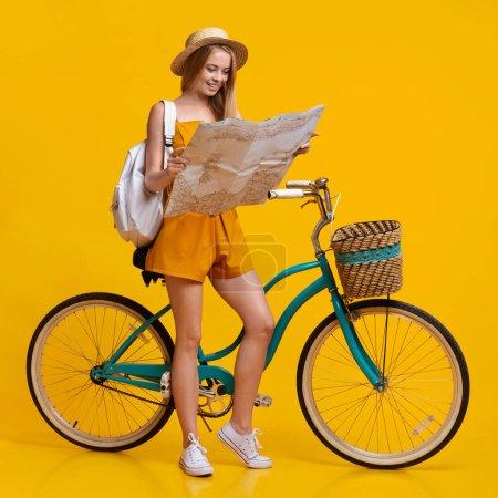 Photo pour À la recherche de nouvelles routes. Happy Teen Girl regardant la carte de la ville, debout à côté de son vélo vintage, fond de studio jaune avec espace libre - image libre de droit