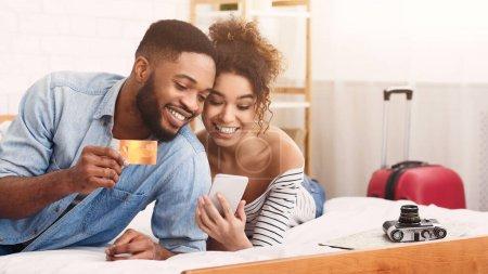 Photo pour Planification des voyages. Couple afro-américain utilisant Smartphone et réservation par carte de crédit billets d'avion dans la chambre à coucher à la maison. Panorama, Espace vide - image libre de droit