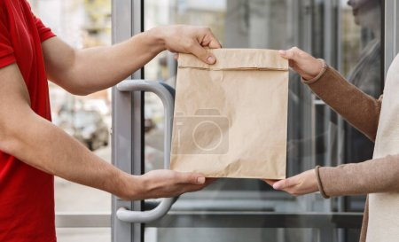 Photo pour Transfert de colis sur le seuil de la maison. Courrier et fille tiennent paquet de papier, vue latérale, gros plan - image libre de droit