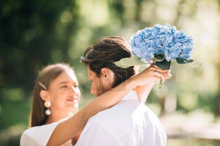 Photo pour Concept de mariage. Aimer les jeunes mariés embrassant, mariée tenant un bouquet de fleurs debout dans le parc pendant la cérémonie. Focus sélectif - image libre de droit