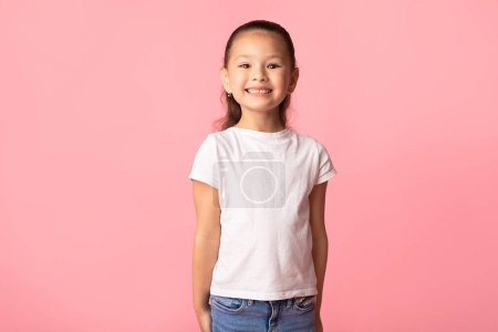 Photo for Portrait of cute casual smiling asian girl posing and looking at camera isolated over pastel pink studio wall, copy space - Royalty Free Image