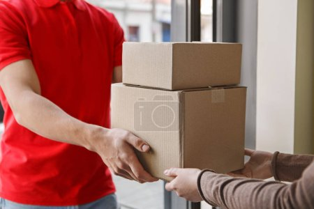 Photo for Receiving parcel at home. Courier gives cardboard boxes to customer at front door - Royalty Free Image