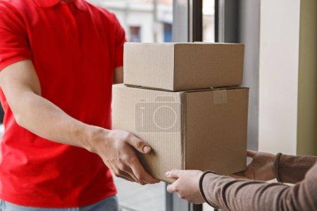 Photo pour Réception de colis à la maison. Courier donne des boîtes en carton au client à la porte d'entrée - image libre de droit
