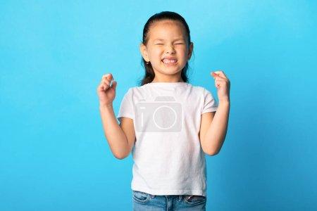 Photo pour Faire un voeu Concept. Petite fille asiatique avec les yeux fermés gardant ses doigts croisés, priant pour la chance, copyspace - image libre de droit