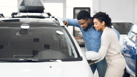 Couple Choosing Car Together Standing Near Vehicle In Showroom, Panorama