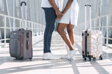 Photo for Happy Reunion. Loving black couple holding hands at airport terminal, meeting after long time apart, cropped image, side view - Royalty Free Image
