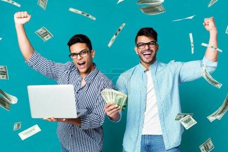 Photo pour Paris sportifs en ligne. Heureux hispaniques gars célébrant le succès avec un ordinateur portable et de l'argent, debout sous la douche de l'argent, émotionnellement réagir pour gagner, collage - image libre de droit