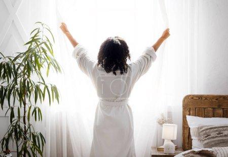Photo pour Bonjour, parfait. Femme méconnaissable vêtue de peignoir blanc ouvrant les rideaux de la fenêtre à la maison, profitant du début de la journée, vue arrière - image libre de droit