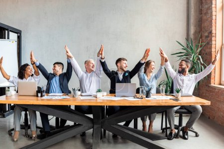 Photo for Business Team Unity. Happy Coworkers Giving High-Five Rejoicing Success At Work Sitting At One Table In Modern Office. - Royalty Free Image