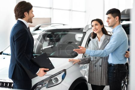Photo for Hugging Couple Buying New Car, Choosing Automobile With Professional Dealer In Luxury Dealership Store. Selective Focus - Royalty Free Image