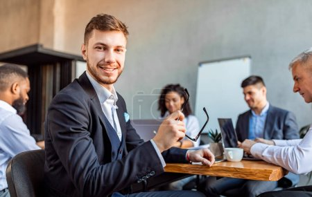 Photo for Corporate Meeting. Young Entrepreneur Smiling To Camera Sitting At Table With Business Partners In Modern Office. Empty Space - Royalty Free Image