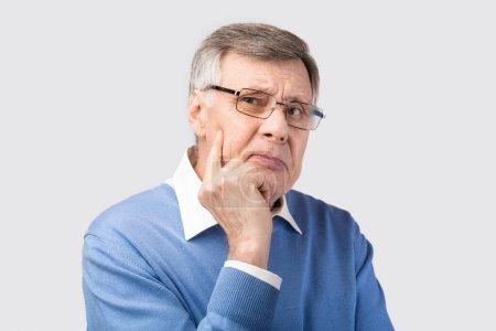 Thoughtful Senior Gentleman Thinking Looking At Camera Posing, Gray Background
