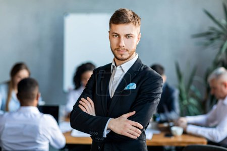Photo pour Concept d'entrepreneuriat. Homme d'affaires confiant debout mains croisées regardant la caméra en face de l'emploi dans le bureau moderne . - image libre de droit