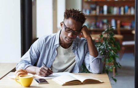 Photo pour Étudiant afro-américain concentré prenant des notes du livre dans un café confortable - image libre de droit