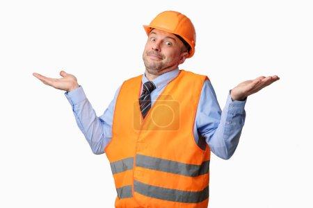 Photo pour Clueless Builder travailleur haussant les épaules en regardant la caméra posant sur fond blanc. Studio Shot - image libre de droit