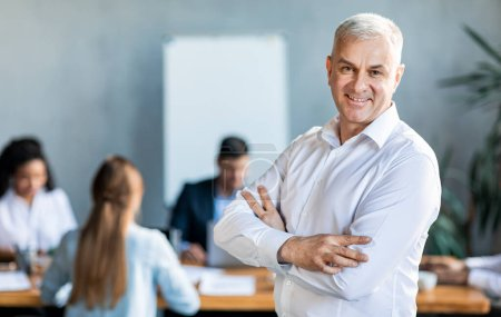 Photo pour Leadership d'entreprise. Homme d'affaires souriant debout mains croisées devant les employés équipe dans le bureau moderne. Espace vide - image libre de droit