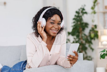 Photo for Digital Music Service. Smiling Black Girl Wearing Wireless Headphones, Listening Favorite Songs On Smartphone, Resting On Couch At Home, Closeup - Royalty Free Image