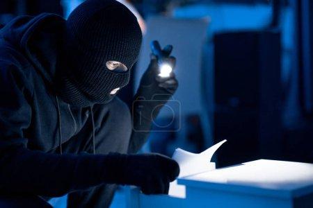Photo pour Concept d'appropriation illicite. Espion masqué tenant la lumière flash et vérifiant les papiers dans le tiroir du bureau dans l'obscurité - image libre de droit