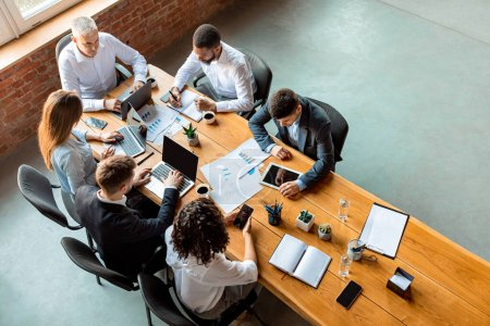Multiracial Business Team Working Sitting At Table In Office, High-Angle