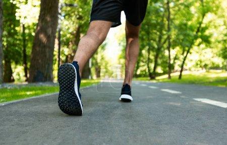 Photo pour Vue aérienne du coureur de marathon lors de son entraînement matinal au parc de la ville, gros plan des jambes - image libre de droit