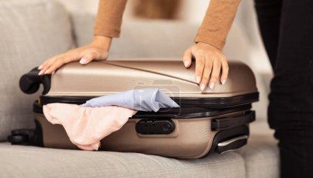 Photo pour Préparation aux vacances. Femme méconnaissable Emballage valise de voyage à la maison. Cultivé, Gros plan - image libre de droit